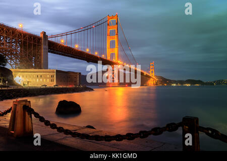 Golden Gate Bridge and chain link fence at Night. - Stock Photo
