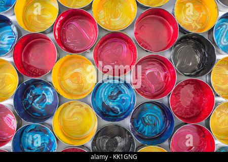 Top view of old CMYK paint cans. Colorful background - Stock Photo