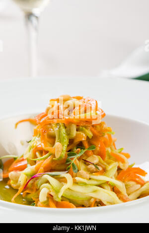 spaghetti from carrots and zucchini with pesto in white plate - Stock Photo