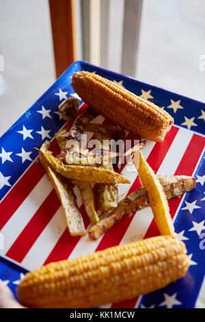 High-angle close-up of a traditional American snack with tasty grilled French fries and corn served on a tray - Stock Photo