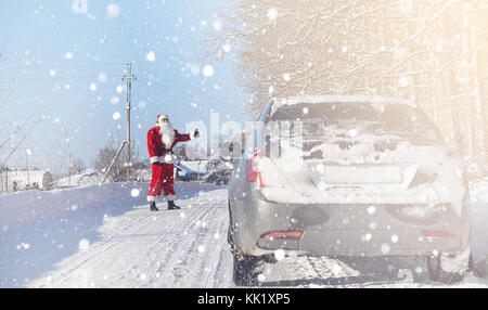 Santa Claus comes with gifts from the outdoor. Santa in a red su - Stock Photo