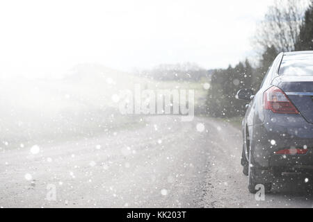 A car on a rural road in the first autumn snow. The first winter - Stock Photo