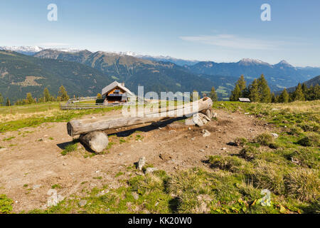 Wooden shepherd lodge on a highland pasture with water trough and Alpine mountain landscape in Western Carinthia, - Stock Photo