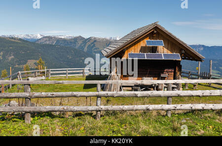 Wooden shepherd lodge with solar panels on a highland pasture with Alpine mountain landscape in Western Carinthia, - Stock Photo
