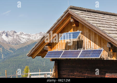 Wooden shepherd lodge with solar panels with Alpine mountain landscape in Western Carinthia, Austria. - Stock Photo