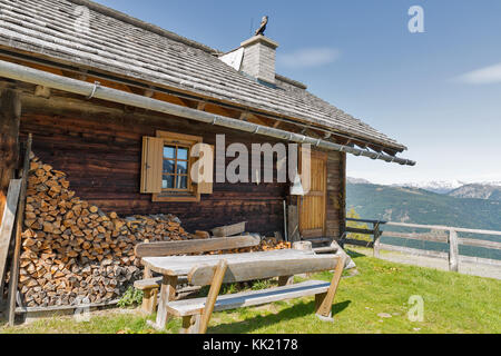 Front yard with wooden table of shepherd lodge on a highland pasture with Alpine mountain landscape in Western Carinthia, - Stock Photo