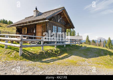 Wooden shepherd lodge on a highland pasture with Alpine mountain landscape in Western Carinthia, Austria. - Stock Photo