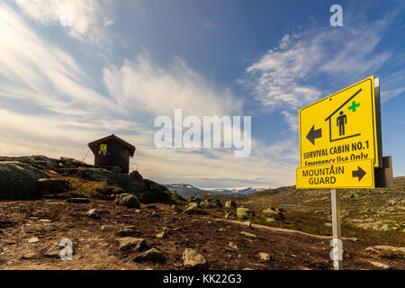 Yellow sign pointing towards the survival cabin in the mountain near Trolltunga in Odda, Norway - Stock Photo