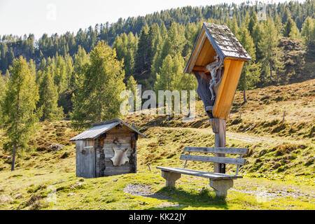 Old wooden crucifix, bench and toilet on a highland pasture with Alpine mountain landscape in Western Carinthia, - Stock Photo