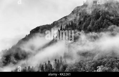 mountain top with misty fog and smoke in Alaska - Stock Photo