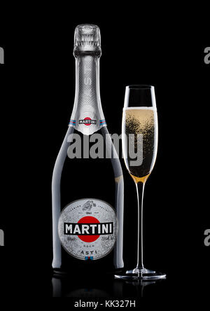 LONDON, UK - November 24, 2017: Bottle and glass of sparkling wine Martini Asti on black background. Produced in - Stock Photo