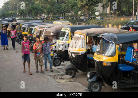 Children stand next to parked auto rickshaws (tuk tuk) in Versova, Mumbai, India - Stock Photo