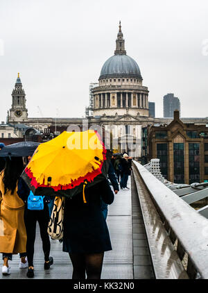 People walking on Millennium Bridge on rainy day with bright umbrellas to St Pauls Cathedral and City of London - Stock Photo