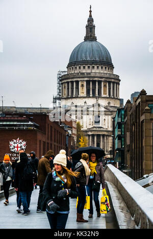 People walking on Millennium Bridge on rainy day to St Pauls Cathedral and City of London school, Thames, England, - Stock Photo