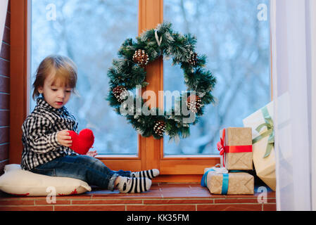 Charming child sits on before window decorated with Christmas wr - Stock Photo