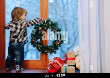 Little boy stands on windowsill looking at winter outside  - Stock Photo