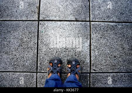 Top view of feet in blue color shoes standing on grey concrete floor