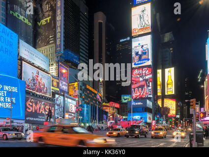 Times Square at night in New York City - Stock Photo