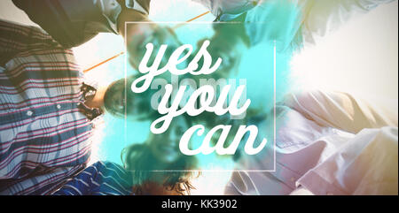 Digitally generated image of yes you can text  against team of businesspeople forming huddle - Stock Photo