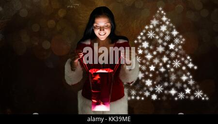 Digital composite of Woman opening gift and Snowflake Christmas tree pattern shape - Stock Photo