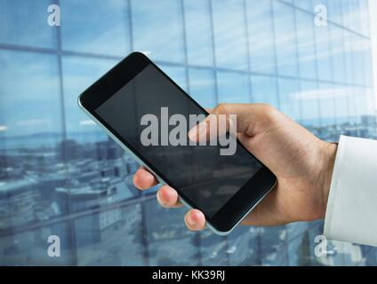 Digital composite of hand holding phone in front of building - Stock Photo