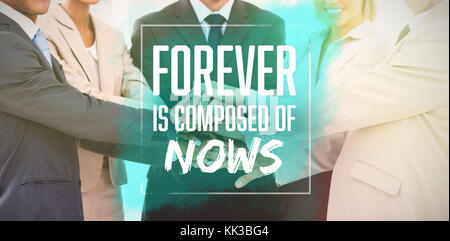 Forever is composed of nows  against group of smiling business people piling up their hands together - Stock Photo