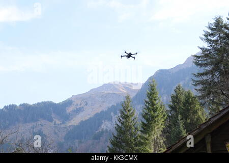 DJI Mavic Pro flying in front of a moutain scenery - Stock Photo