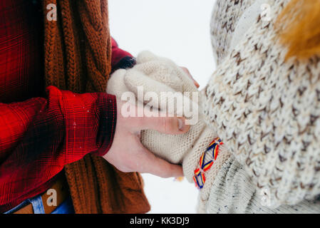 Close-up view of the man hands holding the woman hands in knitted gloves. Winter time. - Stock Photo
