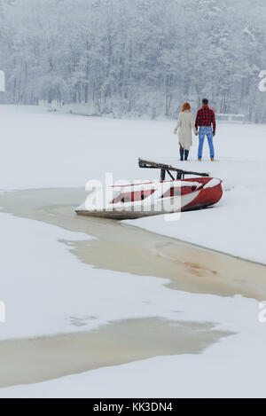 Vertical back view of the couple holding hands in the front of the boat covered with snow in the forest during the - Stock Photo
