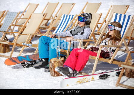 Boy and girl sitting in sun lounger on ski terrain and resting - Stock Photo