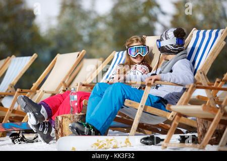 Male and female child enjoys in sun lounger on ski terrain - Stock Photo