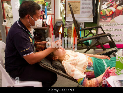 A  Candle Facial is given by Jet Burahem from Narathiwat at a southern-themed market at Klong Phadung Krung Kasem - Stock Photo