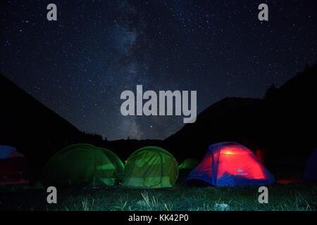 Tents under Milky way in Bunderitsa camping, Pirin mountain, Bulgaria - Stock Photo