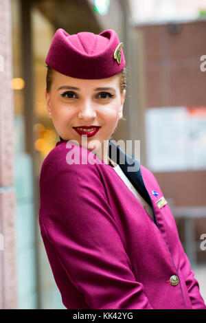 Young attractive female working as cabin crew for Qatar Airways on London layover. Pretty smile, looking happy and - Stock Photo