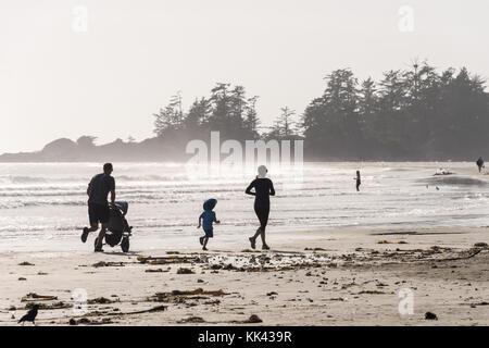 Chesterman beach near Tofino, BC, Canada (September 2017) - Family running on sand. - Stock Photo