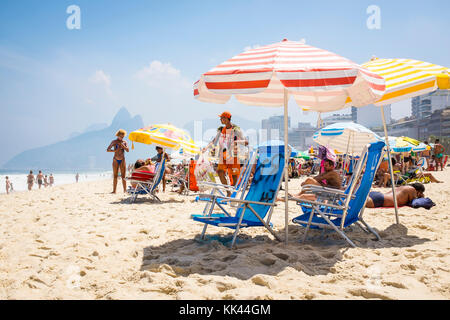 RIO DE JANEIRO - MARCH 06, 2016: A beach vendor selling South American mate iced tea and snacks walks in bright - Stock Photo
