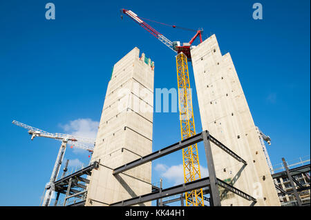 Modern hi-rise towers construction site with cranes under bright blue sky - Stock Photo