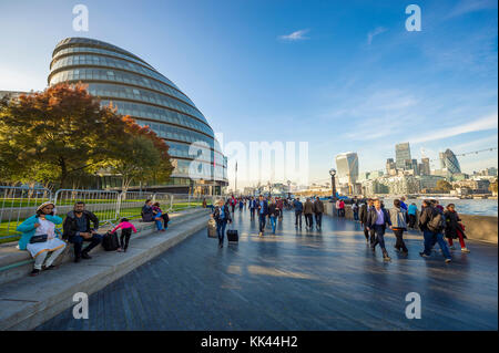 LONDON - OCTOBER 31, 2016: Visitors take advantage of mild autumn afternoon on the south bank of the Thames riverside - Stock Photo