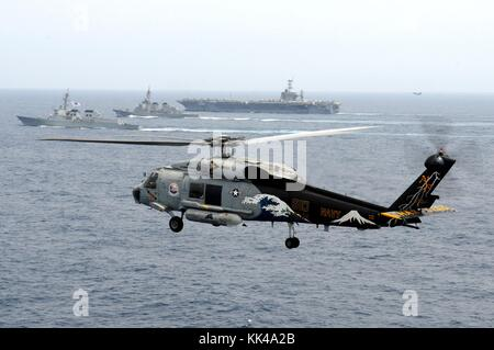 An SH-60F Seahawk helicopter, assigned to the Chargers of Helicopter Anti-Submarine Squadron HS 14, is airborne - Stock Photo