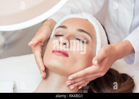 Beautiful woman relaxing during facial massage for rejuvenation  - Stock Photo