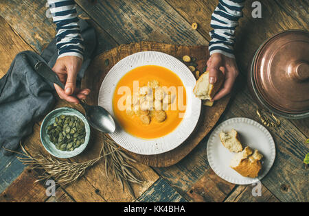 Fall warming pumpkin cream soup with seeds and bread - Stock Photo