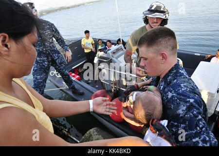 Hospital Corpsman 2nd Class Kyle Turner assists in transporting an infant patient into a Band-Aid boat assigned - Stock Photo