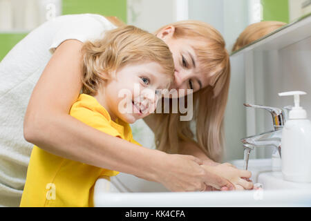 Mother and child son washing their hands in the bathroom. Care and concern for kids. - Stock Photo