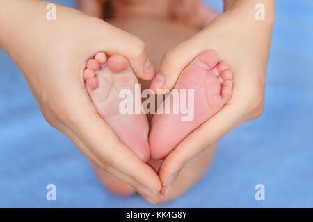 heels of newborn in mother hands forming a heart - Stock Photo