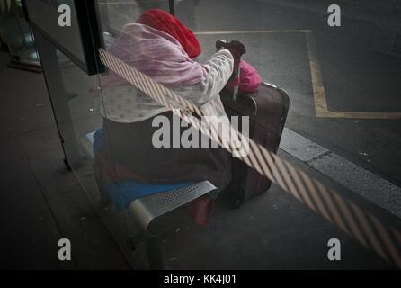 Urban misery. -  02/12/2011  -    -  Urban misery. -  Homeless sleeping under a Bus-stop at Neuilly-sur-Seine.  - Stock Photo