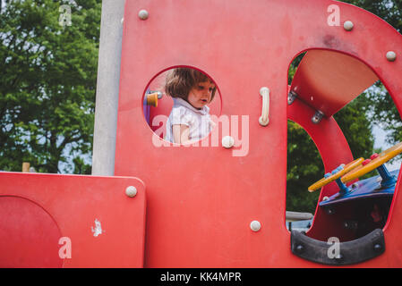 A little girl climbs on playground equipment on summer day - Stock Photo