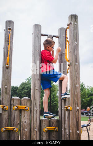 A boy child plays on playground equipment on a summer day - Stock Photo