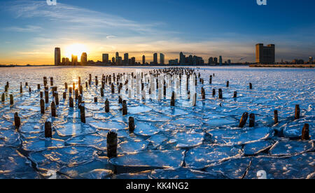 Sunset on the frozen Hudson River with old wood pilings and view on Downtown Jersey City, New Jersey - Stock Photo