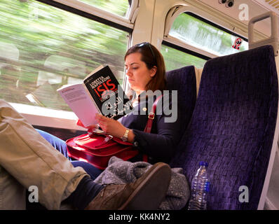 Girl on train reading 'ISIS@ - Stock Photo