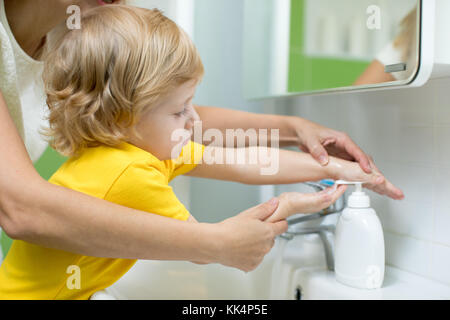 Mother and kid son washing their hands in the bathroom. Care and concern for children. - Stock Photo